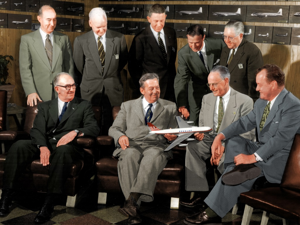 Douglas board with a model of the DC-8. Harold Adams is center back row.