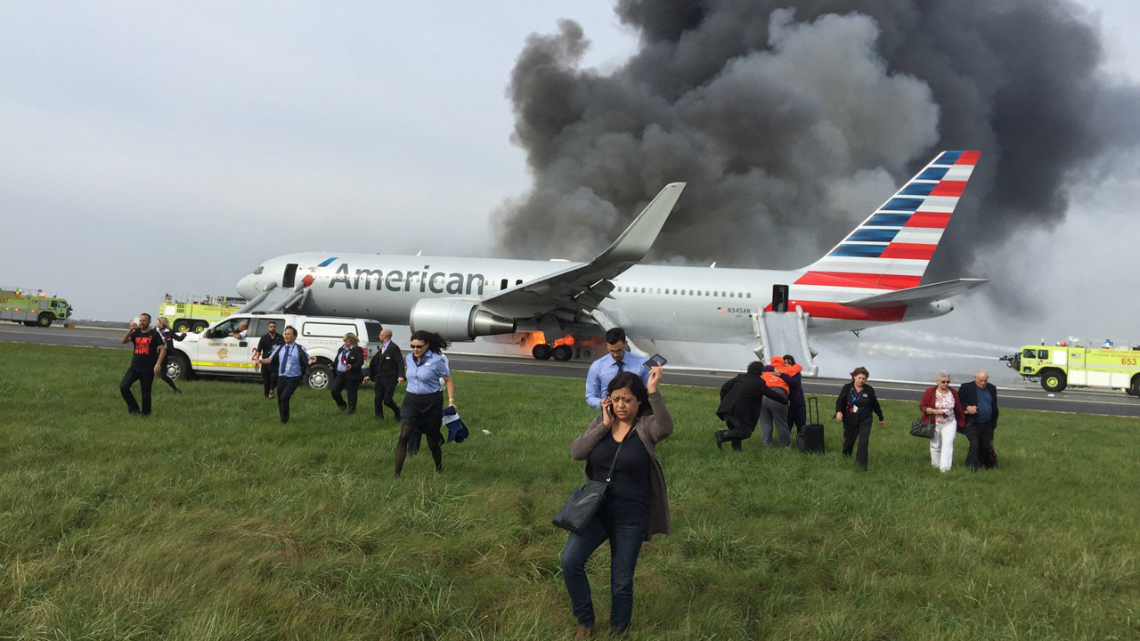 Passengers carry baggage away from plane crash